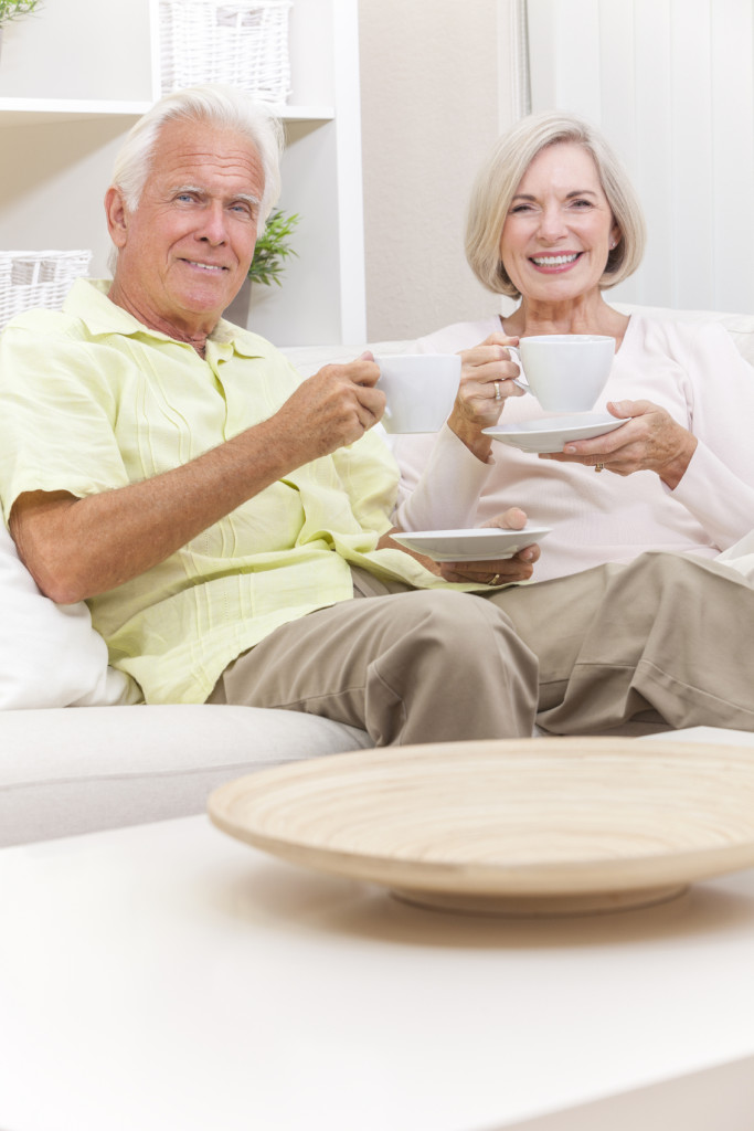 Happy senior man and woman couple sitting together at home on a sofa drinking cups of tea or coffee